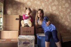 Familj med barn som planerar ändringsstället av uppehållet med staplade lagringsaskar i gammalt hem Arkivbild