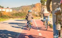 Familj med barn som rider cyklar i naturen Arkivbild