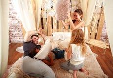 Familj med barn som spelar med kuddar som är hemmastadda på säng royaltyfri foto