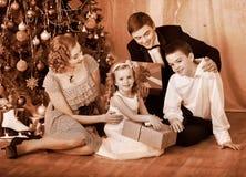 Familj med barn under julgran. Arkivbilder