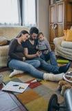 Familj med barnet och den gravida modern som ser minnestavlan royaltyfri foto