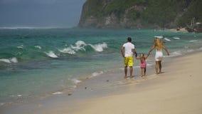 Familj med barnet på stranden lager videofilmer