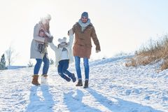Familj med barnet som spelar i snön royaltyfri foto