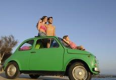 Familj med den små bilen på semester Arkivbild