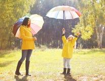 Familj med det färgrika paraplyet som har roligt tyckande om väder Arkivfoton