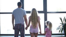 Familj med dotterinnehavhänder vid fönstret lager videofilmer