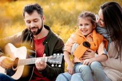 Familj med dottern som kopplar av på en gräs- kulle medan spela för fader arkivbilder