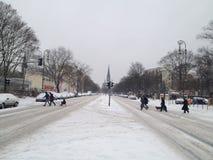 Familj med en pulka som korsar en dold gata för snö med den dstern kyrkan för SÃ-¼ i bakgrunden arkivbilder