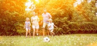 Familj med fotbollbollen i sommar royaltyfria bilder