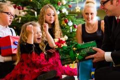 Familj med gåvor på juldag Arkivbild