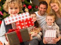 Familj med gåvor som är främre av julgran Arkivbild