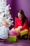 Familj med gåvor som är främre av julgran Arkivfoto