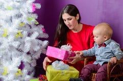 Familj med gåvor som är främre av julgran Royaltyfria Bilder