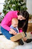 Familj med gåvor som är främre av julgran Royaltyfri Foto