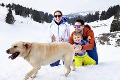 Familj med hunden som har gyckel i snön royaltyfria bilder