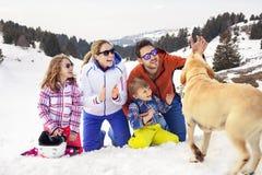 Familj med hunden som har gyckel i snön royaltyfri foto