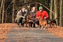 Familj med hundkapplöpning i squattingposition på skogvägen royaltyfria bilder