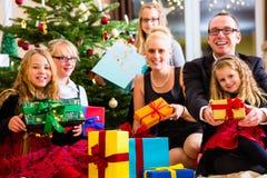 Familj med julklappar under träd Arkivbild