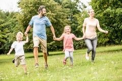 Familj med lyckliga barn Fotografering för Bildbyråer