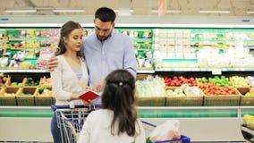 Familj med mat i shoppingvagn på livsmedelsbutiken lager videofilmer