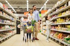 Familj med mat i shoppingvagn på livsmedelsbutiken royaltyfria foton