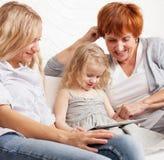 Familj med minnestavladatoren hemma Arkivfoton
