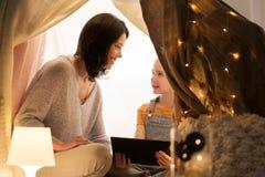 Familj med minnestavlaPC i ungetält hemma fotografering för bildbyråer