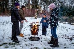 Familj med modern och barn på en lägereld som grillar varmkorvmat Utomhus- plats för vintersnö royaltyfri foto