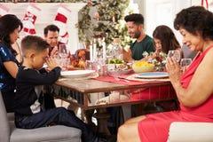 Familj med morföräldrar som säger Grace Before Christmas Meal Arkivbilder