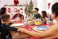 Familj med morföräldrar som säger Grace Before Christmas Meal Arkivfoto