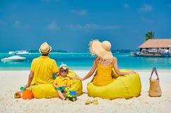 Familj med ?rig pojke tre p? stranden arkivfoton