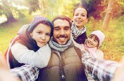 Familj med ryggsäckar som tar selfie och att fotvandra Arkivbilder