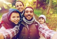Familj med ryggsäckar som tar selfie och att fotvandra Royaltyfria Bilder