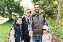 Familj med ryggsäckar som tar selfie och att fotvandra Fotografering för Bildbyråer