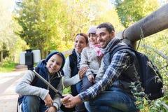 Familj med ryggsäckar som tar selfie och att fotvandra Arkivbild