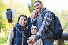 Familj med ryggsäckar som tar selfie och att fotvandra Arkivfoto