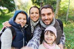 Familj med ryggsäckar som tar selfie och att fotvandra Royaltyfri Bild