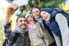 Familj med ryggsäckar som tar selfie vid smartphonen royaltyfri foto