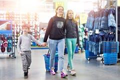 Familj med shoppingvagnen i sportgodslager fotografering för bildbyråer