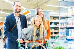 Familj med shoppingvagnen i supermarket Arkivfoton