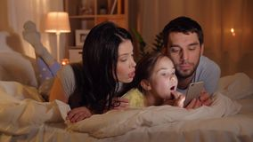 Familj med smartphonen i säng på natten hemma lager videofilmer