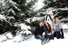 Familj med snögubbejulgranen Arkivfoto