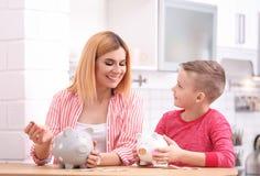 Familj med spargrisar och pengar arkivbilder