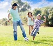Familj med tonåringbarnet som spelar med fotbollbollen Arkivbilder