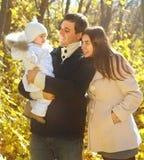 Familj med två döttrar i höstskog Arkivfoto