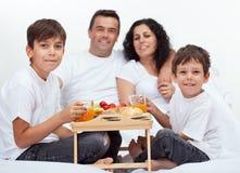 Familj med två pojkar som har frukosten i säng Arkivfoto
