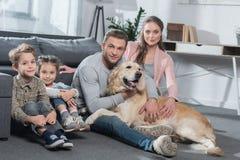 Familj med två ungar och hund som sitter på golv, i vardagsrum och att se royaltyfri bild