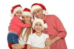 Familj med ungar i santa hattar Royaltyfri Bild