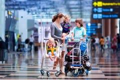 Familj med ungar på flygplatsen Arkivfoton