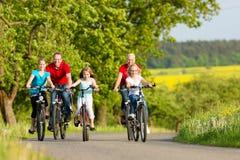 Familj med ungar som cyklar i sommar med cyklar Royaltyfri Bild